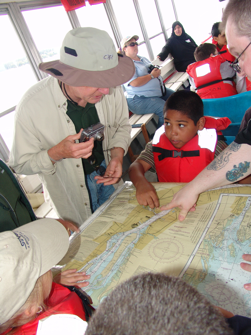 A student points to a location on the nautical map