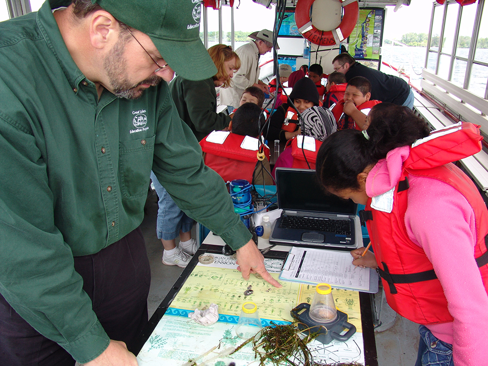 Instructor pointing to a poster that identifies aquatic plants that are present in the river