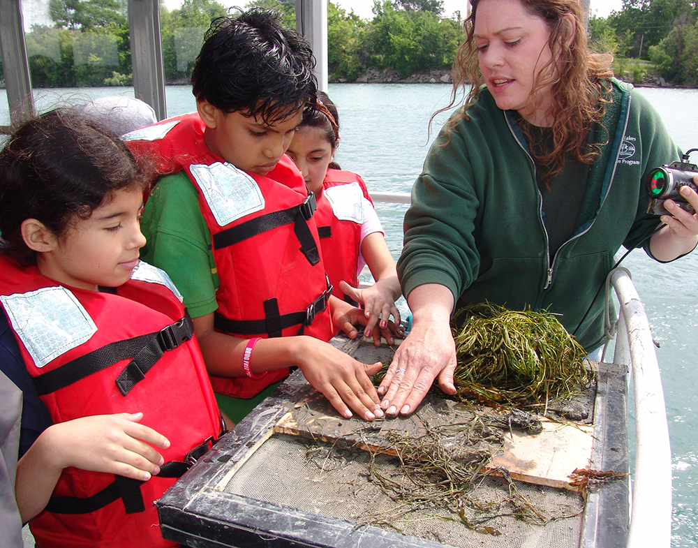 An instructor encourages students to feel the mud and plants pulled up from the river