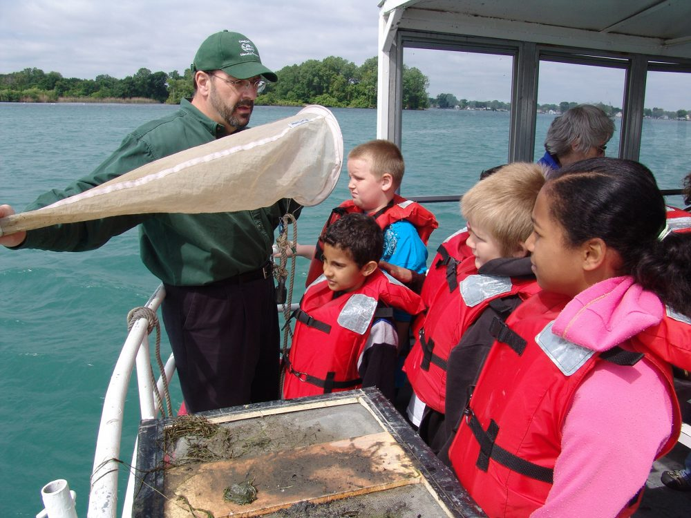 Steve Stewart holds up a sampling net to show students how to collect microorganisms from the water