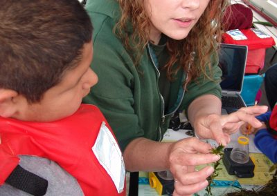 A GLEP instructor shows a student a live plant sample pulled up from the river