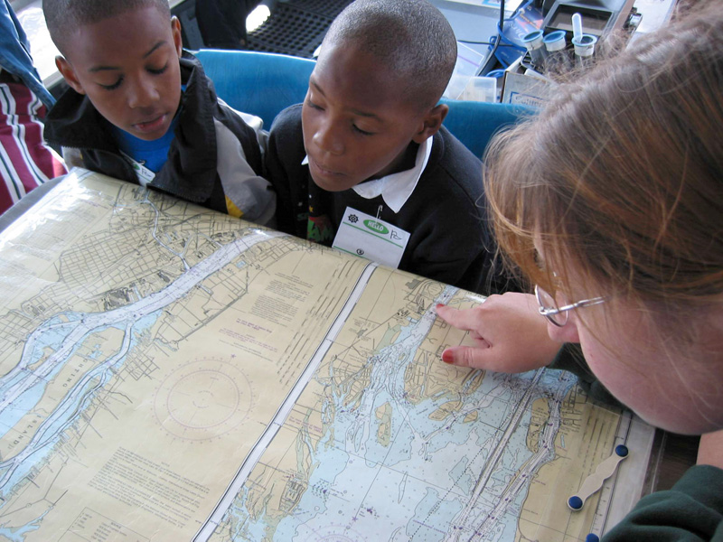two students look at a nautical map of the Detroit River