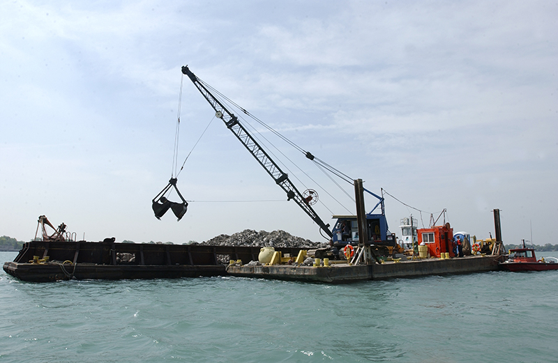 a barge holds substrate that is being put down into the river for reef restoration
