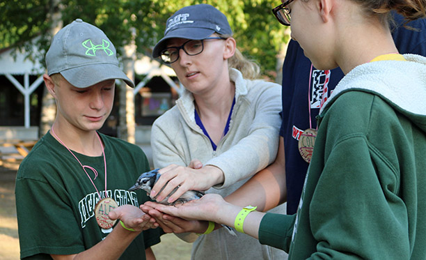 Campers experience science techniques used to sample and study for birds using mist nets with Michigan State University researchers.
