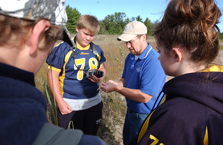 Place Based Education, Alcona Schools, Negwegon State Park, Lake Huron. Brandon Schroeder instructing students on Great Lakes and shoreline habitat.