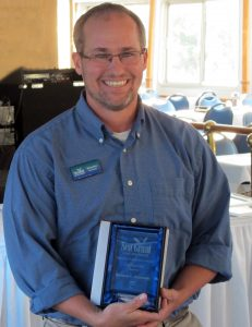 Michigan Sea Grant Extension Educator Brandon Schroeder receives the Great Lakes Sea Grant Network's Distinguished Service Award.