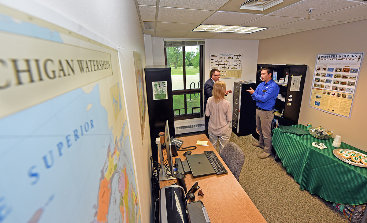 Michigan Sea Grant Extension educator Elliot Nelson speaks with Lake Superior State University Interim Provost David Finley and Aquatics Research Laboratory Co-director Ashley Moerke on June 27 after a ribbon-cutting ceremony at his new office. Photo credit: John Shibley, Lake Superior State University