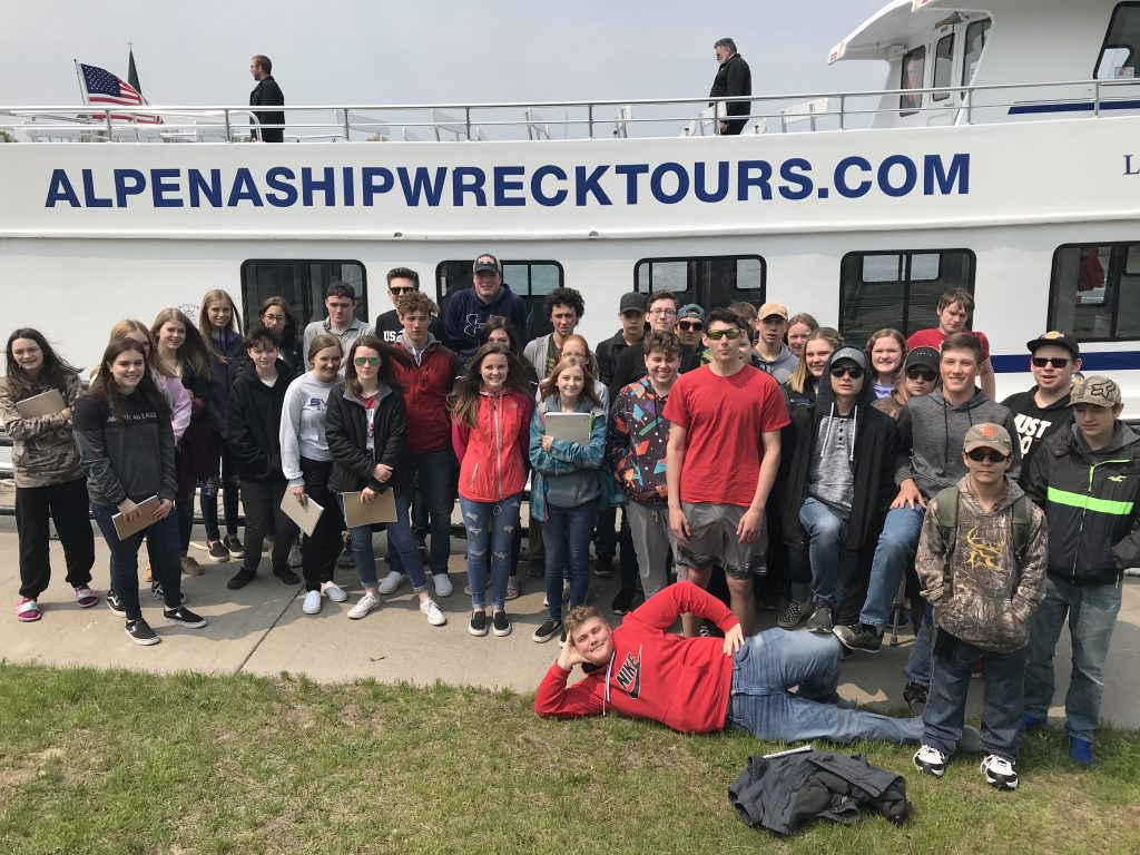 school group standing in front of a tour boat