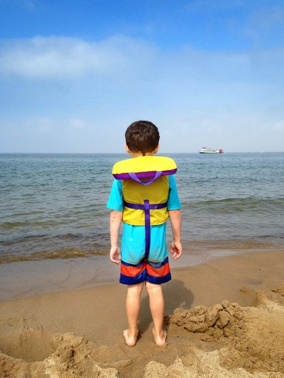 A child wearing a life preserver on beach
