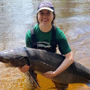 researcher holding a lake sturgeon caught during sampling