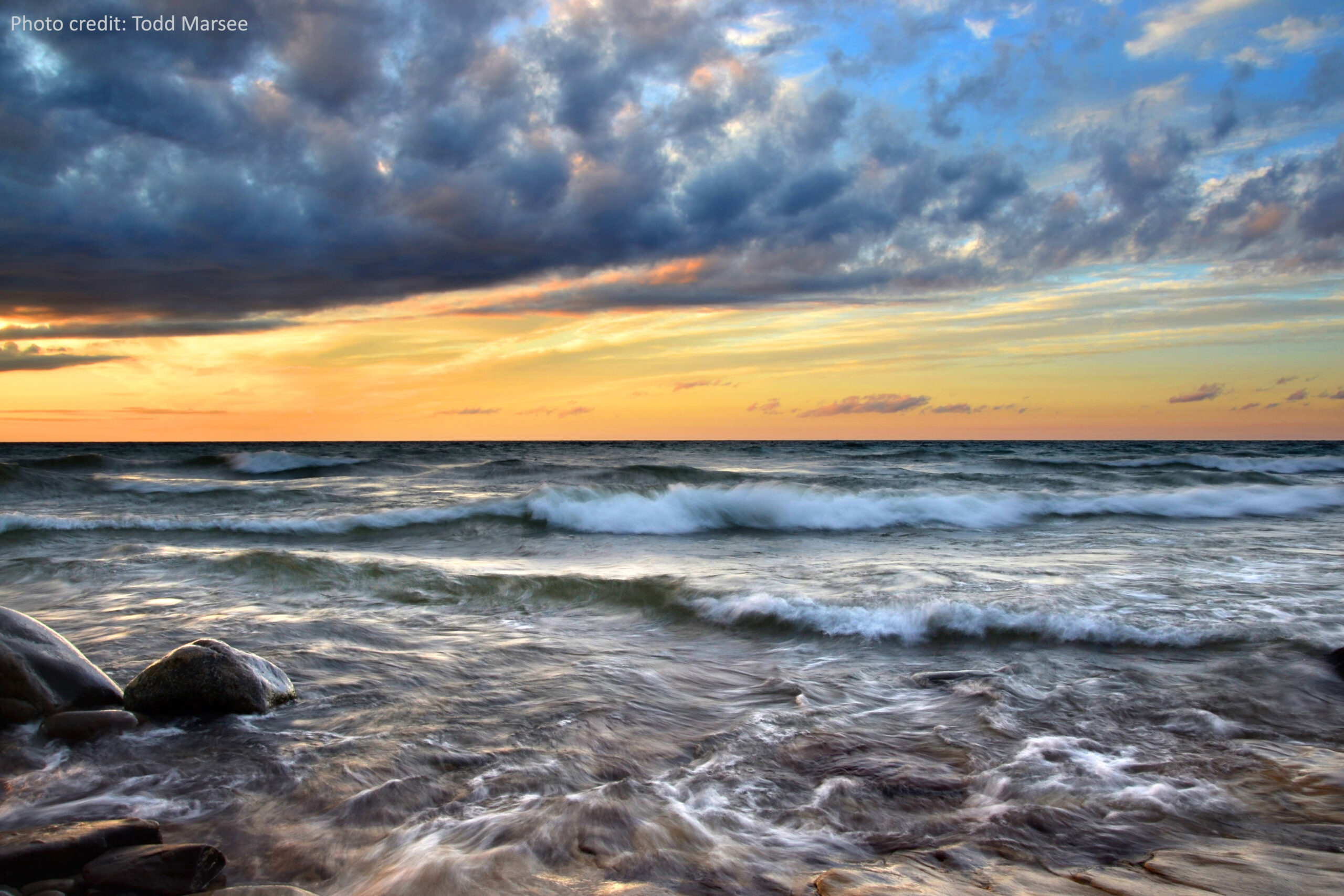 Low waves roiling and crashing on the rocky lakeshore under a sky painted orange by sunset and speckled with clouds.