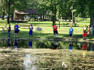 kids at a pond learning how to fish at camp