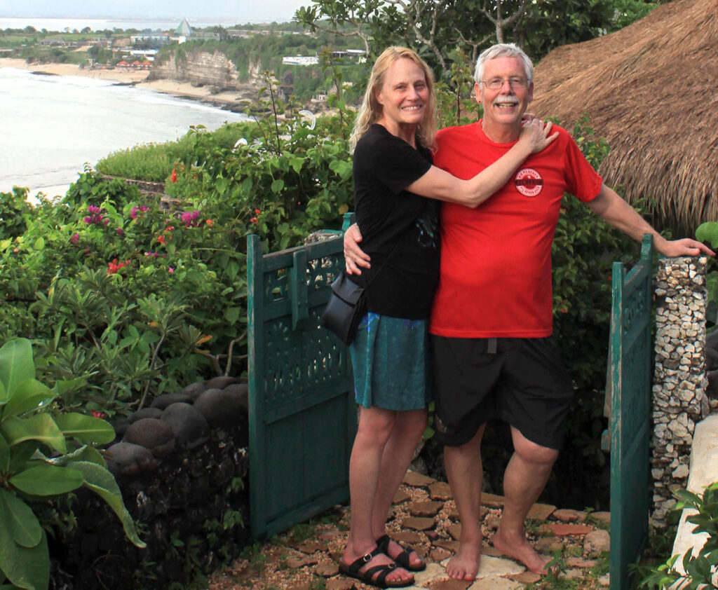 Catherine and Earl with thatched roof cabin